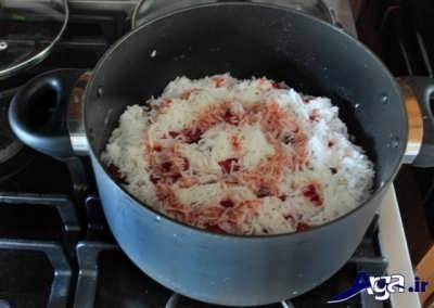 ریختن شربت آلبالو و برنج بر روی آلبالو پلو