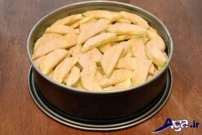 ریختن دارچین و شکر بر روی برش های سیب