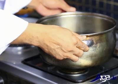 گذاشتن قابلمه آب در روی شعله گاز