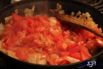 اضافه کردن گوجه به مخلوط سیر و پیاز