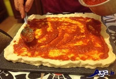 مالیدن سس قرمز بر روی خمیر پیتزا