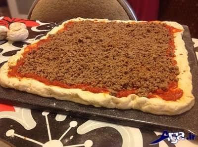 ریختن مایه گوشتی بر روی خمیر پیتزا