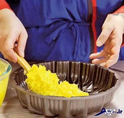 ریختن برنج زعفرانی در درون قالب فر