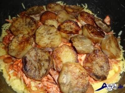 چیدن بادمجان ها و گوشت مرغ بر روی برنج زعفرانی