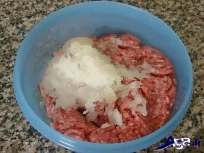 اضافه کردن پیاز رنده شده به گوشت چرخ کرده