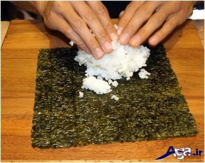 ریختن برنج بر روی برگه سوشی
