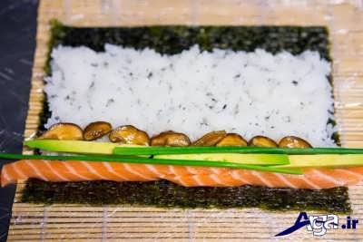 قرار دادن ماهی سالمون و قارچ و پیازچه بر روی برنج سوشی