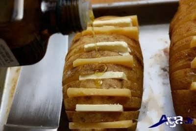 قرار دادن برش های کره و پنیر در لا به لای سیب زمینی برش داده شده