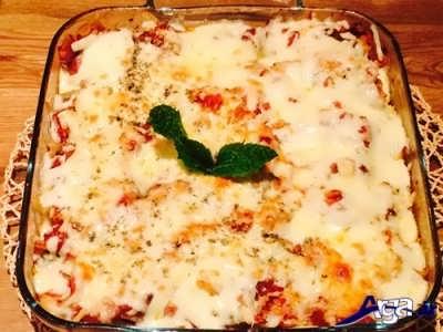 ریختن پنیر پیتزا بر روی پاستاهای صدفی شکم پر