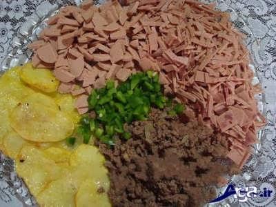 ریختن سوسیس و گوشت و فلفل دلمه ای بر روی سیب زمینی ها ورق ورق شده