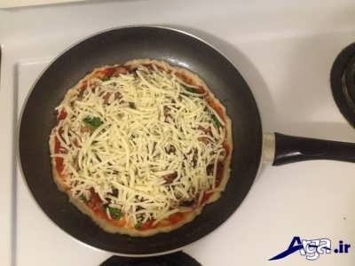ریختن پنیر پیتزا روی مواد پیتزا