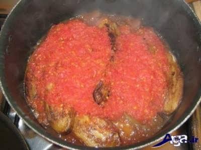 اضافه کردن بادمجان ها به مخلوط گوجه رنده شده و رب