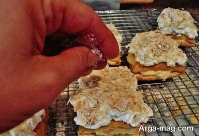 ریختن خمیر خرد شده روی شیرینی ناپلئونی