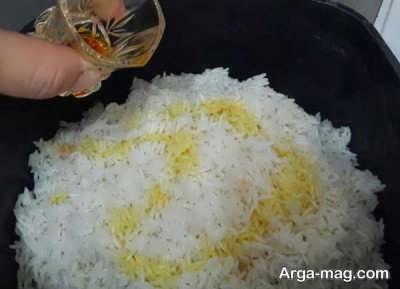 ریختن زعفران و روغن زیتون روی برنج