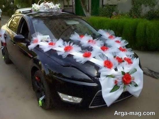 تزیین زیبای ماشین عروس مشکی رنگ با گل های قرمز و پاپیون سفید