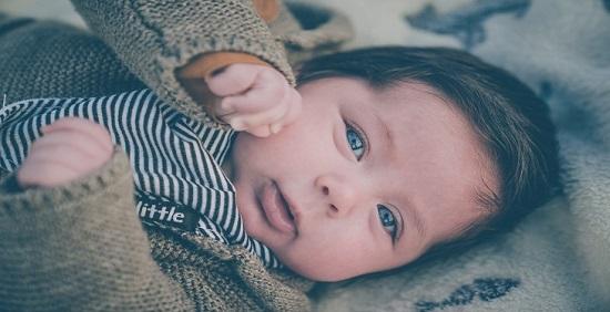 نوزاد با چشمان آبی در کالسکه زیبا